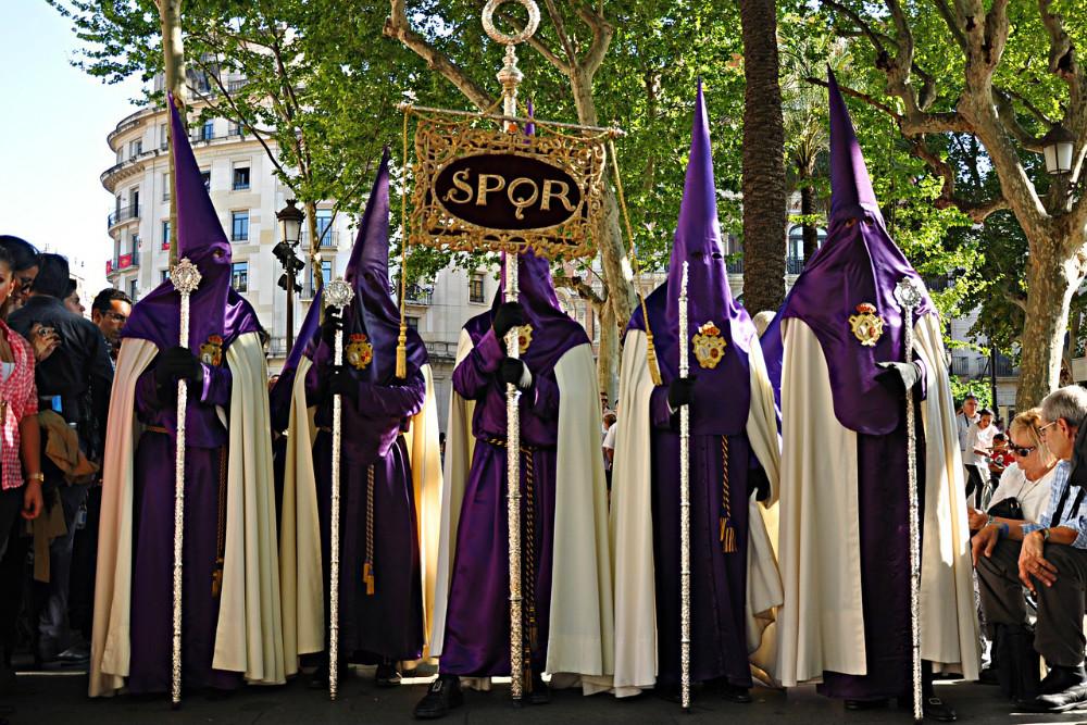 Nazarenos con estandartes durante la Semana Santa en Sevilla