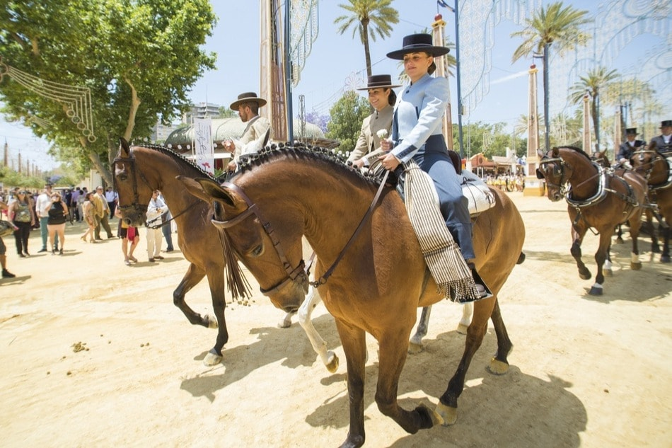 Ruiters en paarden rijden tijdens de paardenmarkt in Jerez