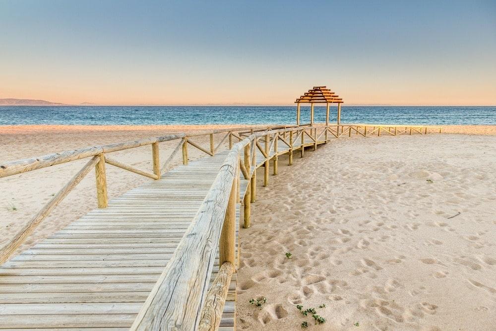 Houten voetpad op het strand van Faro de Trafalgar