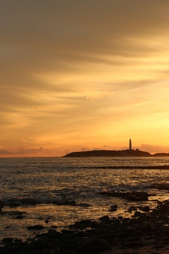 Vuurtoren van Trafalgar aan de horizon bij zonsondergang